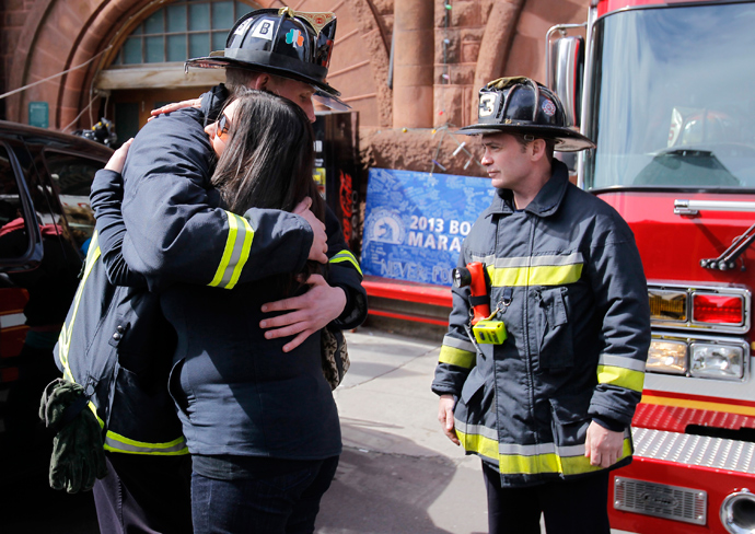 A woman embraces a Boston Firefighter shortly before a moment of silence for the victims of the Boston Marathon bombings marking a week to the day of the bombings at a memorial on Boylston Street in Boston, Massachusetts April 22, 2013 (Reuters / /Jessica Rinaldi)