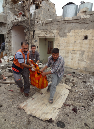 Iraqis carry human remains wrapped in a blanket at the site of a bombing in the northern city of Kirkuk on May 15, 2013 (AFP Photo / Marwan Ibrahim)