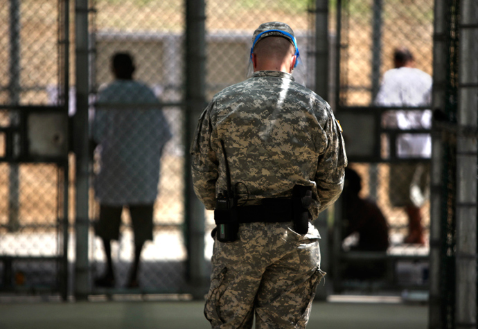 n this photo, reviewed by the U.S. military, and shot through glass, a guard watches over Guantanamo detainees inside the exercise yard at Camp 5 detention facility at Guantanamo Bay U.S. Naval Base, Cuba (Reuters / Brennan Linsley)