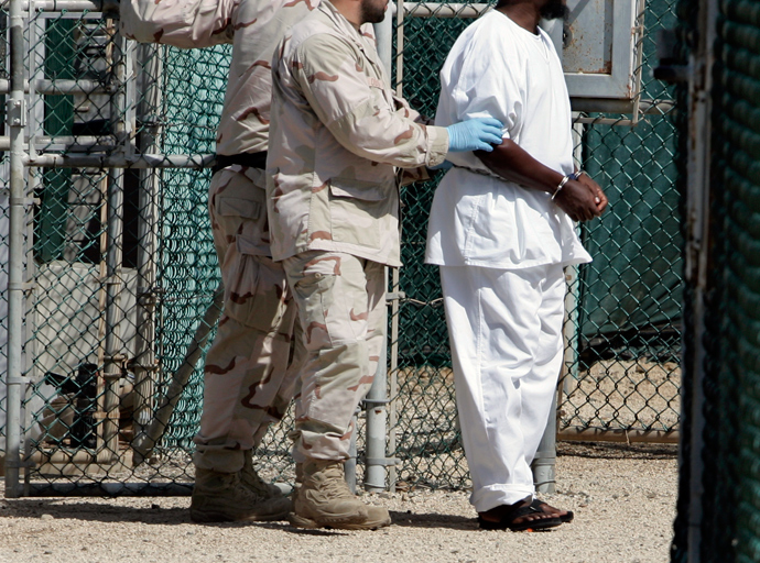 """A detainee is escorted by U.S. Navy guards in Camp Four, the facility containing the """"most compliant"""" detainees, at the Guantanamo Bay Naval Station in Guantanamo Bay, Cuba (Reuters / Joe Skipper)"""