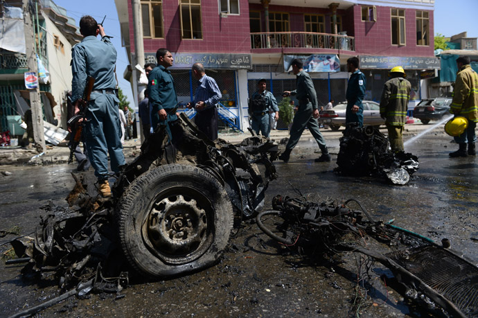 Afghan policemen walk around the destroyed suicide car bomb at the site of a suicide attack in Kabul on May 16, 2013. (AFP Photo)