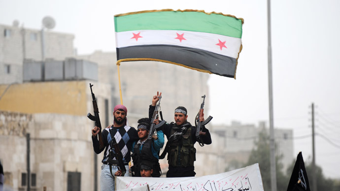 Syrian rebels raise their weapons under a pre-Baath Syrian flag currently used by the opposition during an anti-regime protest in the northern city of Aleppo on March 22, 2013. (AFP Photo)