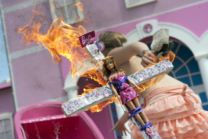 A Barbie doll fixed on it as she runs during a protest action in front of the so called Barbie Dreamhouse - the first life-sized giant mansion dedicated to the doll in Europe, ahead of its opening near the Alexanderplatz in Berlin. (AFP Photo / Barbara Sax)