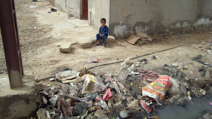 An Iraqi child sits next to a garbage dump and running sewege outside his family home in Baghdad's poor neighbourhood of Hay Ur. (AFP Photo)