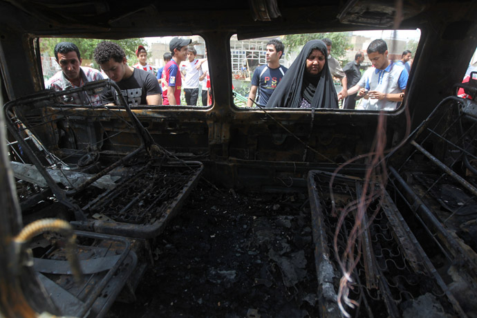 Iraqis inspect a burnt vehicle at the site of a car bombing at a market in Baghdad's impoverished district of Sadr City on May 16, 2013 as at least eight people were killed in blasts across the country. (AFP Photo)