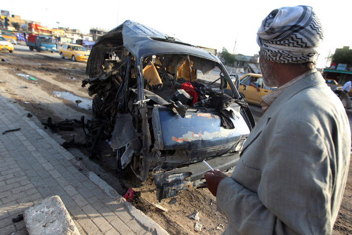 An Iraqi man looks at the remains of a vehicle at the scene of a car bomb explosion the previous days in Baghdad's Sadr City district on May 16, 2013. (AFP Photo)