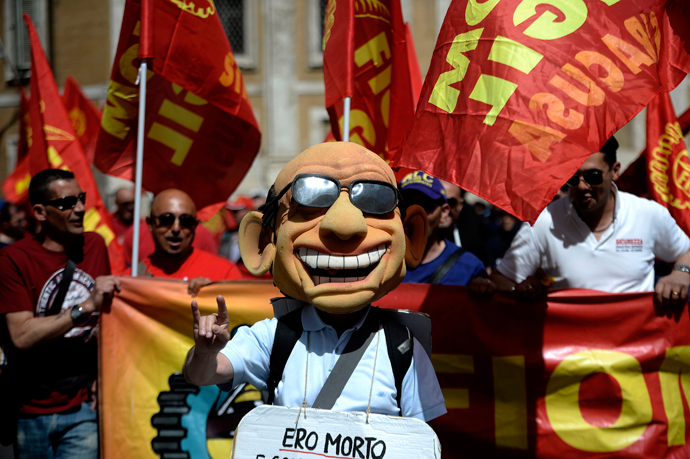 A man wearing a mask resembling former Prime Minister Silvio Berlusconi demonstrates during the left-wing Italian metalworkers' union FIOM rally in downtown Rome on May 18, 2013 (AFP Photo / Filippo Monteforte)
