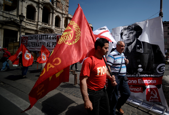 Demonstrators walk pass a banner showing German Chancellor Angela Merkel dressed as a Nazi during the left-wing Italian metalworkers' union FIOM rally in downtown Rome on May 18, 2013 (AFP Photo / Filippo Monteforte)