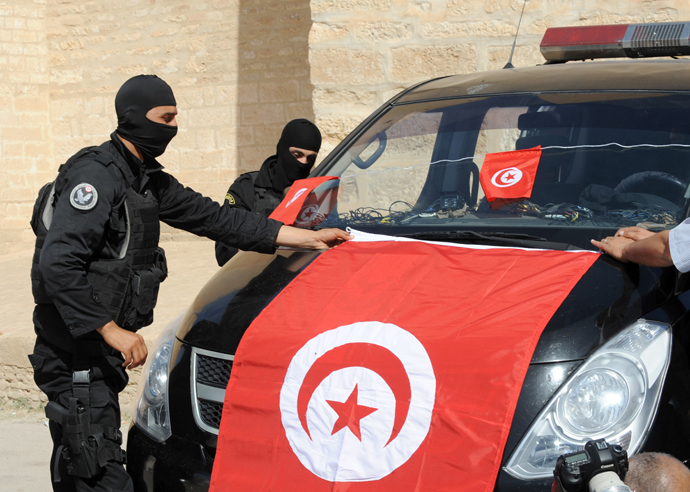 Tunisian Police Special Unit agents fix a national flag on their vehicle in front of the Okba Ibn Nafaa mosque in the central Tunisian city of Kairouan on May 19, 2013 (AFP Photo / Fethi Belaid)