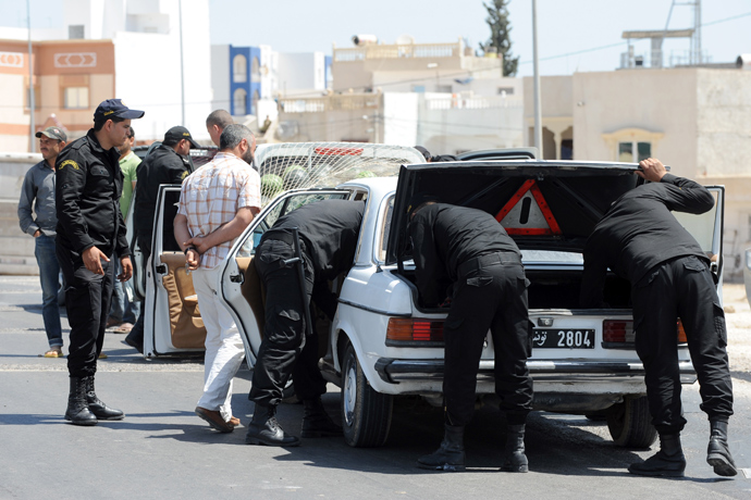 Tunisian Police Special Unit agents check vehicles driving on a road leading the central Tunisian city of Kairouan on May 19, 2013 (AFP Photo / Fethi Belaid)