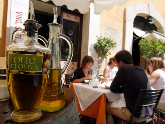 Diners sit near bottles of olive oil at a restaurant in Rome (Reuters / Dario Pignatelli)