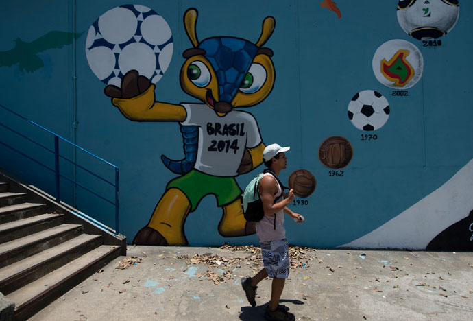 "A man walks next to a mural depicting ""Fuleco"", the mascot of the Brazil 2014 FIFA World Cup.(AFP Photo / Christophe Simon)"