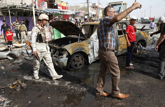 Iraqi citizens and soldiers inspect the scene of one of two car bombs that exploded in the main southern port city of Basra on May 20, 2013, that killed several and wounded dozens more, security and medical officials said, as a wave of attacks struck across the country. (AFP Photo / Ramzi Al-Shaban)
