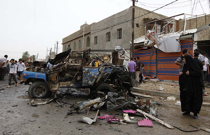 Residents gather at the site of a car bomb attack in the Kamaliya district in Baghdad May 20, 2013. (Reuters / Mohammed Ameen)