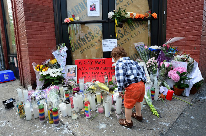 A young boy offers flowers at a makeshift shrine set on the location where Mark Carson, 32, a gay man, was shot dead in what police are calling a hate crime in Greenwich Village in New York, May 20, 2013. (AFP Photo / Emmanuel Dunand)