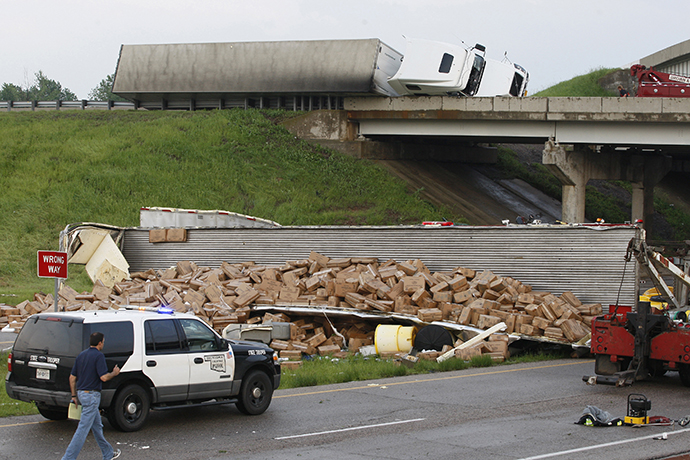 A semi-tractor trailer (top) rests on its side against the guard rails on Interstate 40 as another trailer lies broken open on the road below after falling from I-40, following a tornado strike near Highway 177 north of Shawnee, Oklahoma May 19, 2013. (Reuters / Bill Waugh)