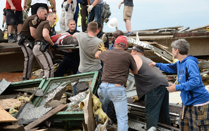 Rescue workers help free one of 15 people trapped in a medical building at the Moore hospital complex after a tornado tore through the area of Moore, Oklahoma May 20, 2013 (Reuters / Gene Blevins)
