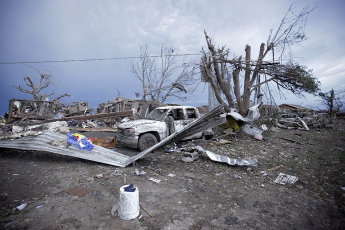 Piles of debris and cars lie around a home destroyed by a tornado May 21, 2013 in Moore, Oklahoma. (AFP Photo / Brett Deering)