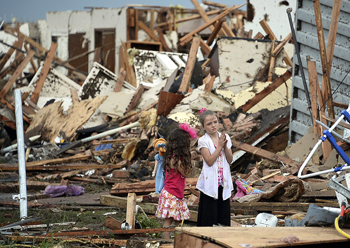Two girls stand in rubble after a tornado struck Moore, Oklahoma, May 20, 2013. (Reuters / Gene Blevins)