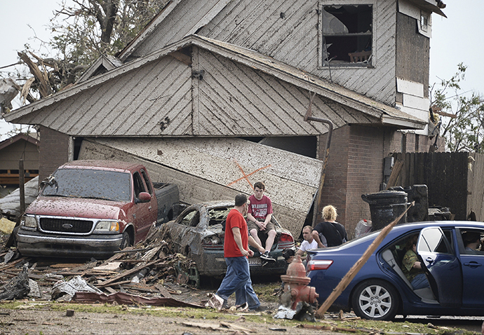 People are seen next to a damaged house and vehicles along a street after a huge tornado, in Moore, Oklahoma May 20, 2013. (Reuters / Gene Blevins)