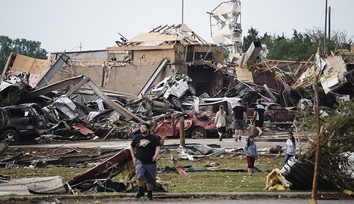 People walk near destroyed buildings and vehicles after a tornado struck Moore, Oklahoma, near Oklahoma City, May 20, 2013. (Reuters / Gene Blevins)