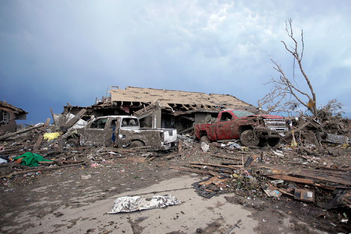 Piles of debris and cars lie around a home destroyed by a tornado May 21, 2013 in Moore, Oklahoma (Brett Deering / Getty Images / AFP)