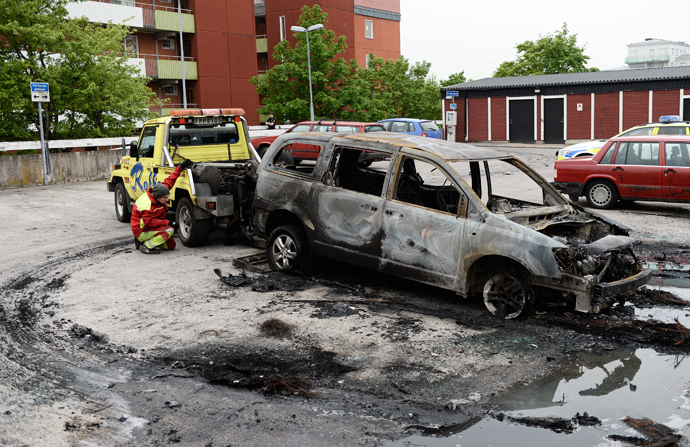 A burned-out van is prepared for removal after youths rioted in Husby, northern Stockholm on May 21, 2013 (AFP Photo / Jonathan Nackstrand)