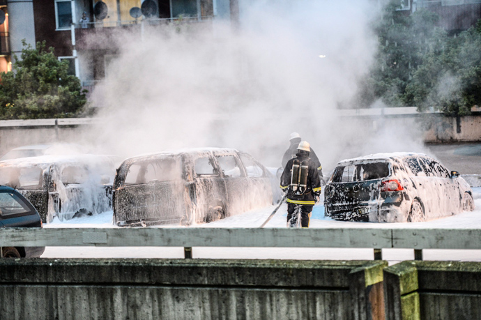 Policemen extinguish burning cars after youths rioted in Husby, northern Stockholm on May 20, 2013 (AFP Photo / Fredrik Sandberg / Scanpix Sweden/ Sweden out)