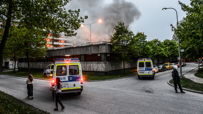 Policemen secure an apartment building after youths rioted in Husby, northern Stockholm on May 20, 2013 (AFP Photo / Fredrik Sandberg / Scanpix Sweden/ Sweden out)