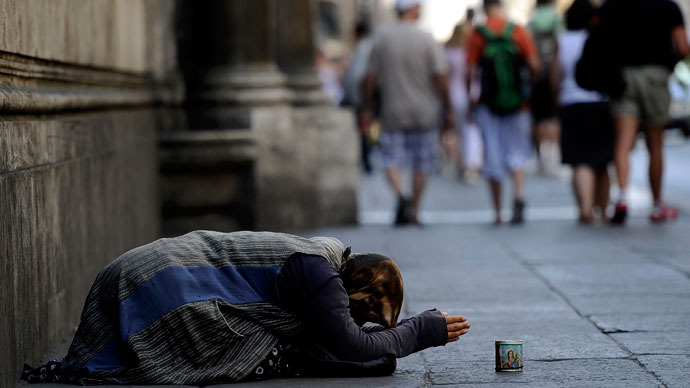 : Tourist pass by a street beggar in central Rome.(AFP Photo / Filippo Monteforte)