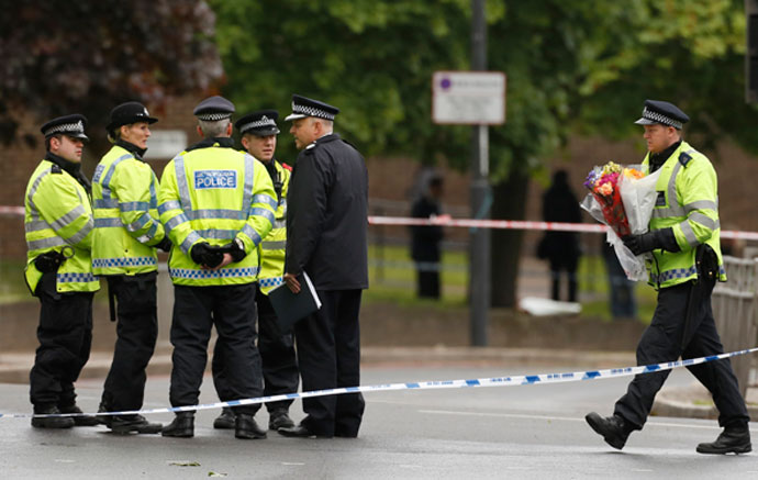 A police officer carries flowers near the scene of the killing of a British soldier in Woolwich, southeast London May 23, 2013.(Reuters / Luke MacGregor)