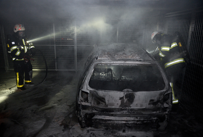 Firemen extinguish a burning car parked in an indoor garage in the Stockholm suburb of Tureberg after youths rioted in several different suburbs for a fourth consecutive night on May 24, 2013 (AFP Photo / Jonathan Nackstrand)
