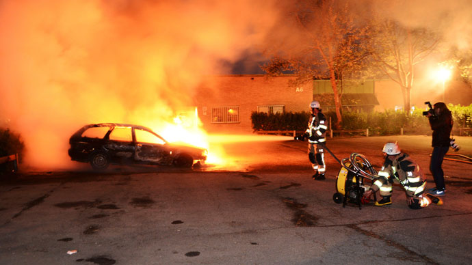 Firefighters extinguish a burning car, following riots in the Stockholm suburb of Kista late May 21, 2013.(Reuters / Fredrik Sandberg)