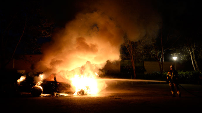 Firemen extinguish a burning car in Kista after youths rioted in few differant suburbs around Stockholm on May 21, 2013.(AFP Photo / Jonathan Nackstrand)