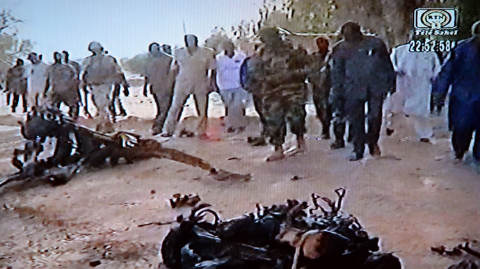This video grab taken from Niger's TV public channel Tele Sahel on May 23, 2013 shows people standing in front of wreckage of the suicide bomber's motor vehicle, at the Agadez army base, northern Niger, following car bombings in Niger in which at least 20 people died (AFP Photo / Tele Sahel)