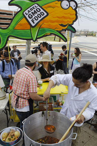 Servers Austin Ginsberg and Jonathan Bisagni feed soup to fellow protesters during an eat-in in front of the U.S. Food and Drug Administration's Center for Food Safety and Applied Nutrition in College Park. (Reuters / Gary Cameron)