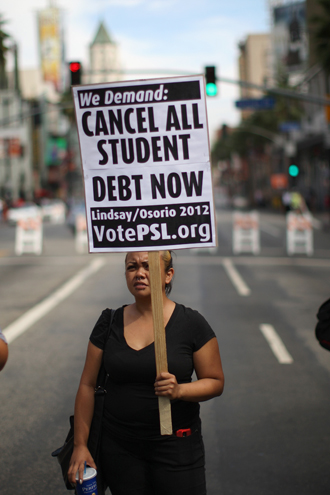 A woman holds a placard on Hollywood Boulevard while protesting the rising costs of student loans for higher education on September 22, 2012. (AFP Photo / David Mcnew)