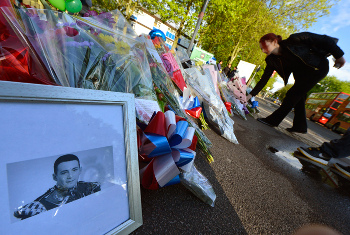 A picture of victim Drummer Lee Rigby, of the British Army's 2nd Battalion The Royal Regiment of Fusiliers is displayed with flowers left by mourners outside an army barracks near the scene of his killing in Woolwich, southeast London May 23, 2013 (Reuters / Toby Melville)