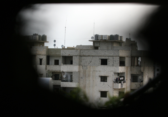 A damaged building is seen through a hole in a wall in the Sunni district of Bab al-Tabbaneh following overnight clashes with the Alawite neighbourhood of Jabal Mohsen in the northern Lebanese port city of Tripoli, on May 25, 2013 (AFP Photo / Ghassan Sweidan)