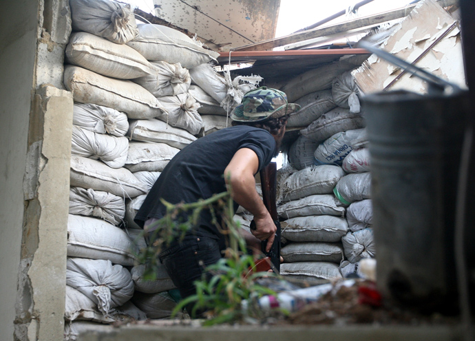 A Lebanese gunmen stands guard behind a barricade in the Sunni district of Bab al-Tabbaneh following overnight clashes with the Alawite neighbourhood of Jabal Mohsen in the northern Lebanese port city of Tripoli, on May 25, 2013 (AFP Photo / Ghassan Sweidan)