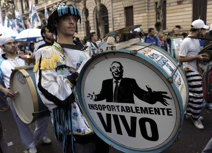 "A supporter of Argentine President Cristina Fernandez de Kirchner plays a bass drum displaying a portrait of late Argentine President Nestor Kirchner and reading ""Unbearably alive"" while arriving to Plaza de Mayo square in Buenos Aires on May 25, 2013. (AFP Photo / Juan Mabromata)"