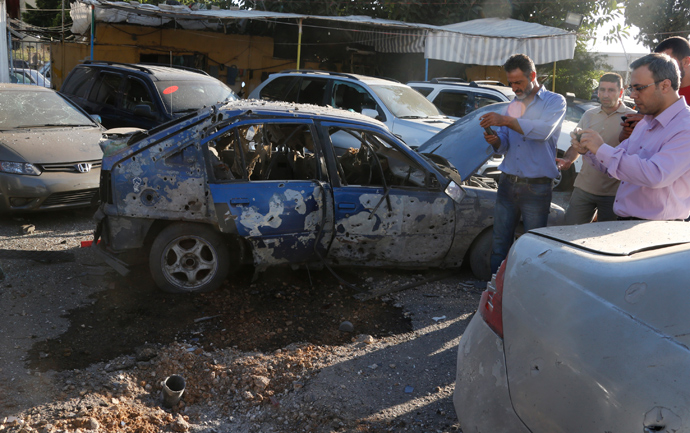 Residents inspect the remain of one of the two rockets that hit their residential area in Beirut suburbs May 26, 2013 (Reuters / Mohammed Azakir)