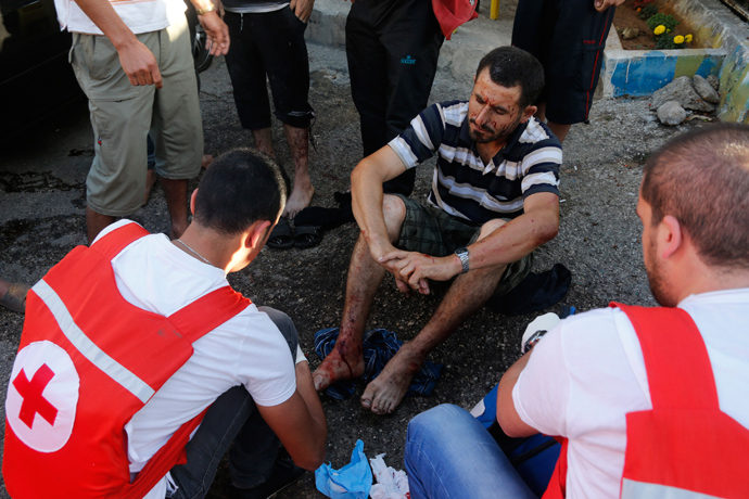 Members of Lebanese Red Cross treat a wounded man after two rockets hit his house in Beirut suburbs May 26, 2013 (Reuters / Mohammed Azakir)
