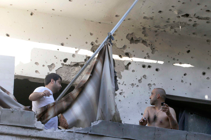 Two men inspect their damage house after two rockets hit their area in a Beirut suburbs May 26, 2013 (Reuters / Mohammed Azakir)