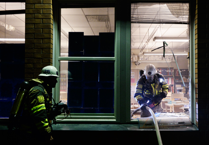 Firemen extinguish a burning school room in the Stockholm suburb of Tensta after youths rioted in few different suburbs around Stockholm and Sweden on May 25, 2013 (AFP Photo)