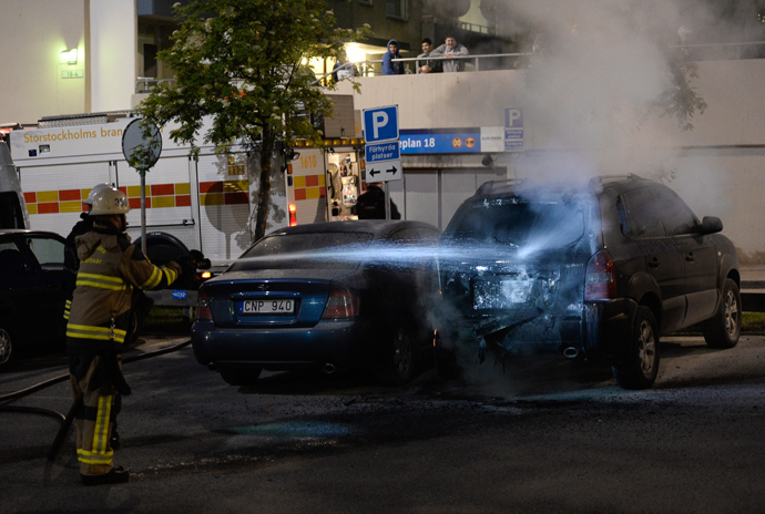 Firemen extinguish a burning car in the Stockholm suburb of Tensta after youths rioted in few different suburbs around Stockholm and Sweden on May 24, 2013 (AFP Photo)