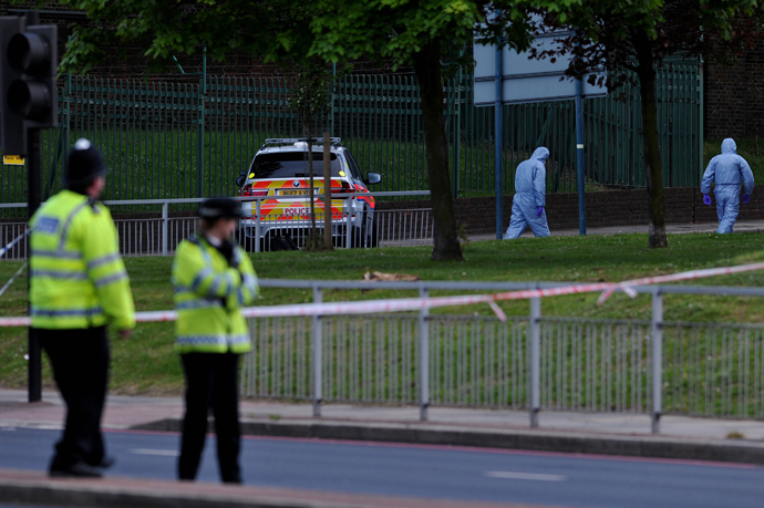 Police forensics officers search a cordoned off area in Woolwich, east London, on May 22, 2013, following an incident in which one man was killed and two others seruiously injured (AFP Photo / Carl Court)