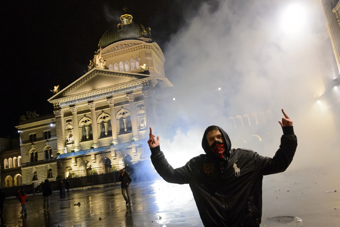 "A man reacts after the riot police flooded with tear gas in front of the Swiss House of Parliament on late May 25, 2013 in the center of Switzerland's capital Bern during the 3rd edition of ""Tanz Dich Frei"" (Dance Yourself Free) a politically-tinged techno parade and mass unauthorised rally (AFP Photo / Fabrice Coffrini)"