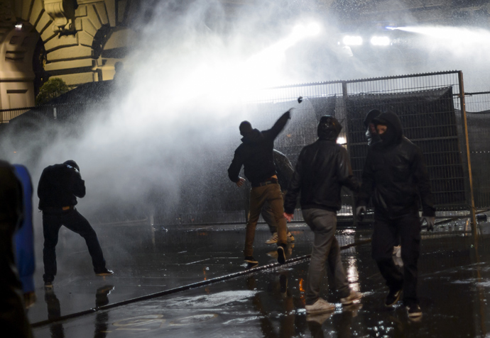 """Members of the Black bloc are sprayed by a water cannon in front of the Swiss House of Parliament on late May 25, 2013 in the center of Switzerland's capital Bern during the 3rd edition of """"Tanz Dich Frei"""" (Dance Yourself Free) a politically-tinged techno parade and mass unauthorised rally (AFP Photo / Fabrice Coffrini)"""