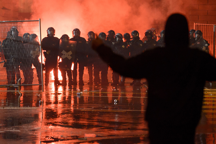"""A member of the Black bloc faces riot police in front of the Swiss House of Parliament on late May 25, 2013 in the center of Switzerland's capital Berne during the 3rd edition of """"Tanz Dich Frei"""" (Dance Yourself Free) a politically-tinged techno parade and mass unauthorised rally (AFP Photo / Fabrice Coffrini)"""